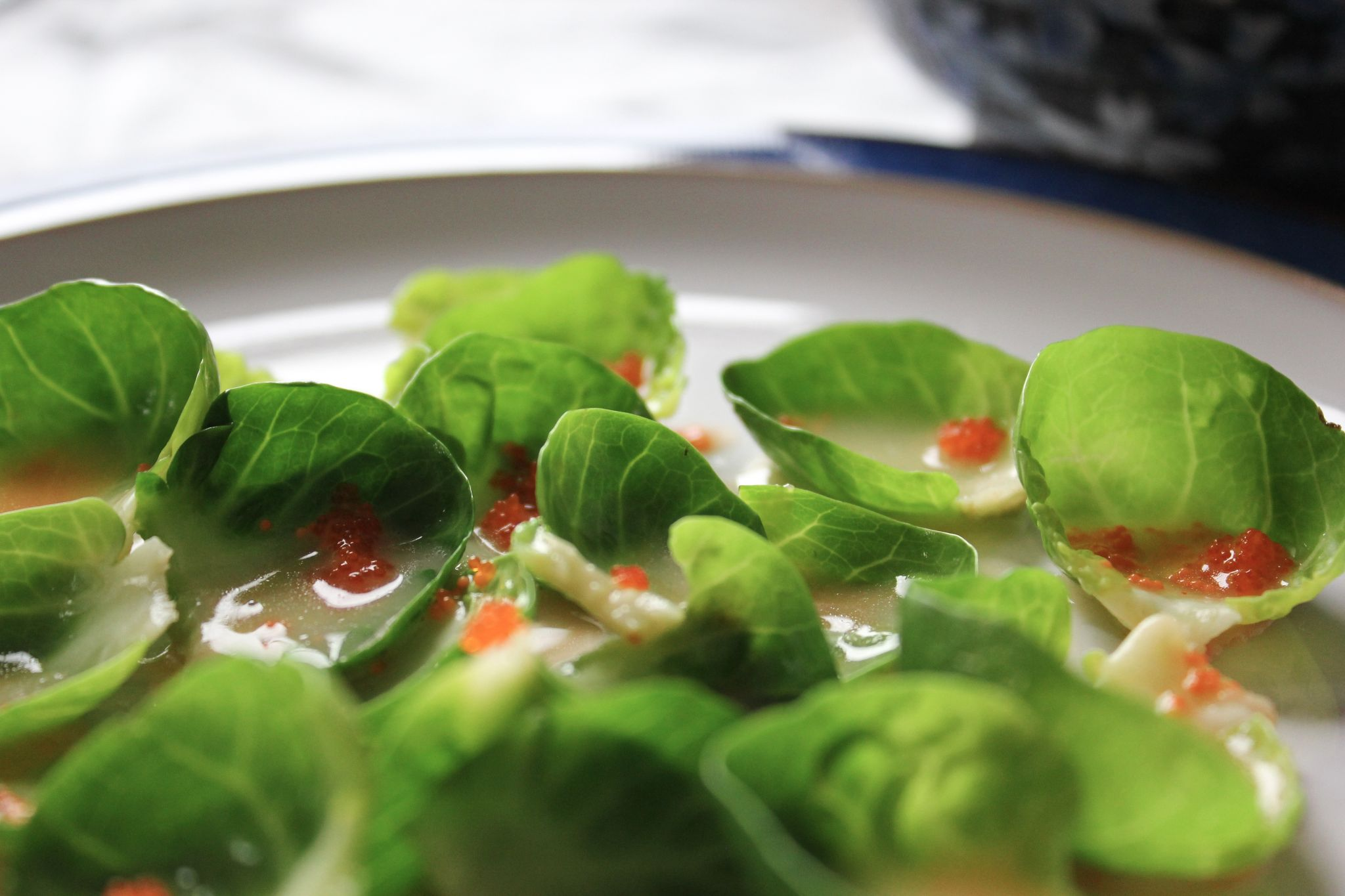 A plate of brussel sprouts leaves, drenched in white buttery sauce, with some orange fish roe.